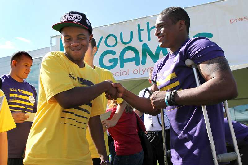 by: JAIME VALDEZ - Timothy Jackson, who is a student at Sunset High School, shakes hands with 2011 NCAA wrestling champion Anthony Robles at the Special Olympics Oregon Youth Games held Saturday at the Tiger Woods Center on the Nike World Headquarters campus.