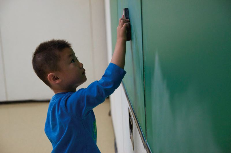 by: TRIBUNE PHOTO: ADAM WICKHAM - Alden Ton erases the blackboard at a Chinese language school in Chinatown. A PSU study says despite high-profile successes, local Asian-Americans are confronting institutional racism on a county-wide scale.