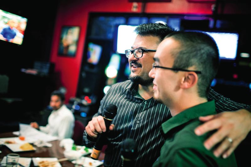 by: TRIBUNE PHOTO: CHRISTOPHER ONSTOTT - Joseph Santos-Lyons of Asian advocacy organization APANO joins Kyle Weismann-Yee at karaoke night. APANO is demanding that more government resources be dedicated to the Asian community.