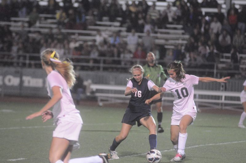 by: MATTHEW SHERMAN - Lake Oswego's Emily Elott battles for a loose ball in the Lakers's first league win last week, a 2-1 victory over West Linn.