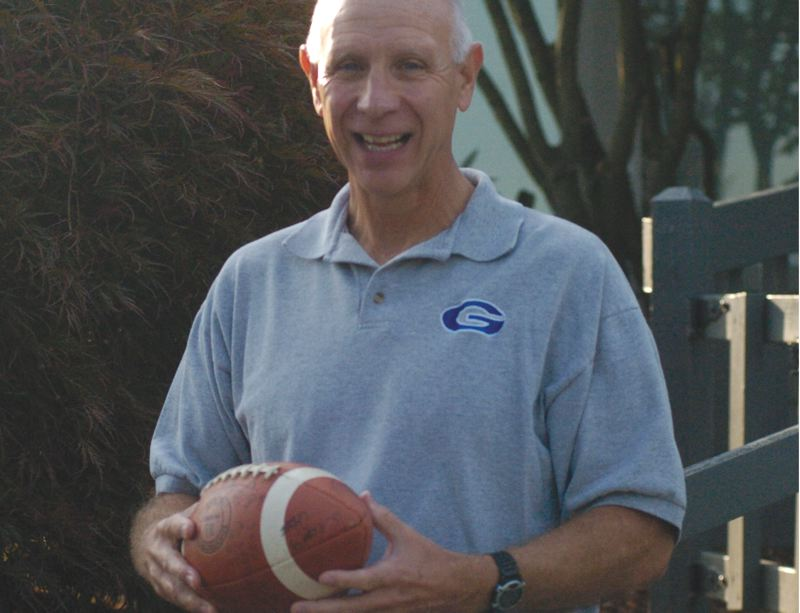 by: THE OUTLOOK: DAVID BALL - Former Gresham High head football coach Gary Stautz holds a signed football from the 1982 state championship game. The Gophers beat Lebanon 13-12 to claim the crown in front of more than 15,000 fans at Civic Stadium.