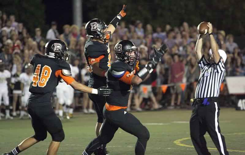 by: MILES VANCE - OUR BALL - Beaverton players (from left) Kiuna Talalamotu, Dylan Erice and Evan Colorito celebrate a takeaway during their 23-13 loss to Southridge at Beaverton on Friday.