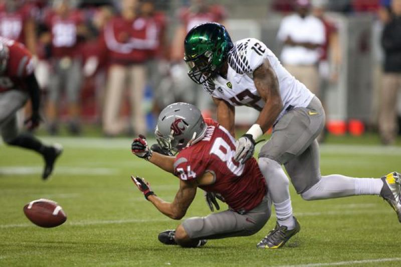 by: JESSE BEALS - Oregon's Brian Jackson knocks the ball away from Washington State's Gabe Marks as the Ducks beat the Cougars 51-26 Saturday in Seattle.