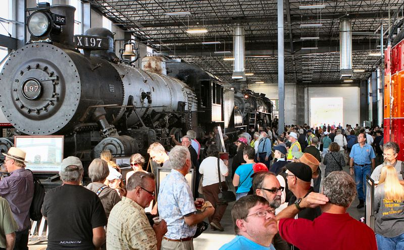 by: DAVID F. ASHTON - Guests gaze at the historic locomotives, now parked safely inside the brand new Portland Rail Heritage Center near OMSI.