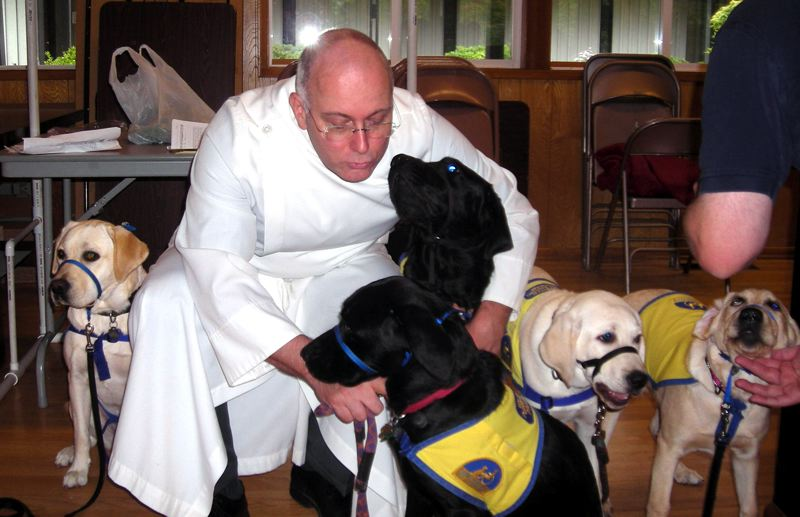 by: CONTRIBUTED PHOTO - Father Scott Dolph, rector of St. Aidan Episcopal Church, blesses several animals each year during a service honoring St. Francis of Assisi. This year's ceremony will take place at 10 a.m. Sunday, Oct. 7.