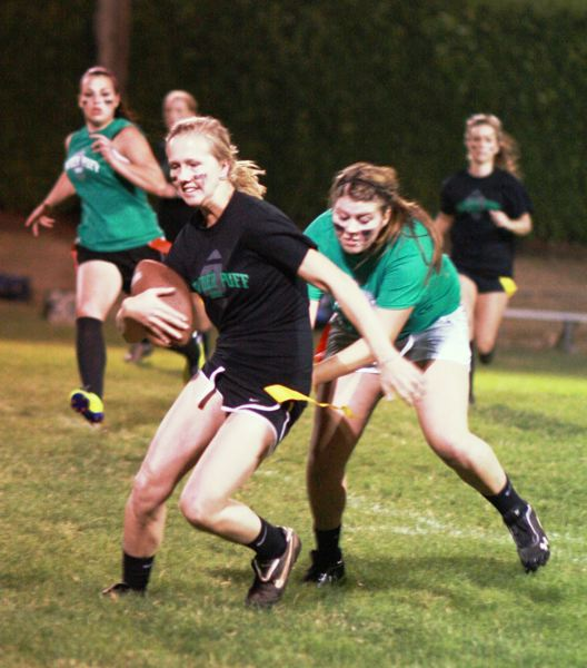 by: PHOTOS BY JOEY NIBBE - Estacada senior Molly Kammeyer runs the ball during the powder puff football game, which ended at 21-21.