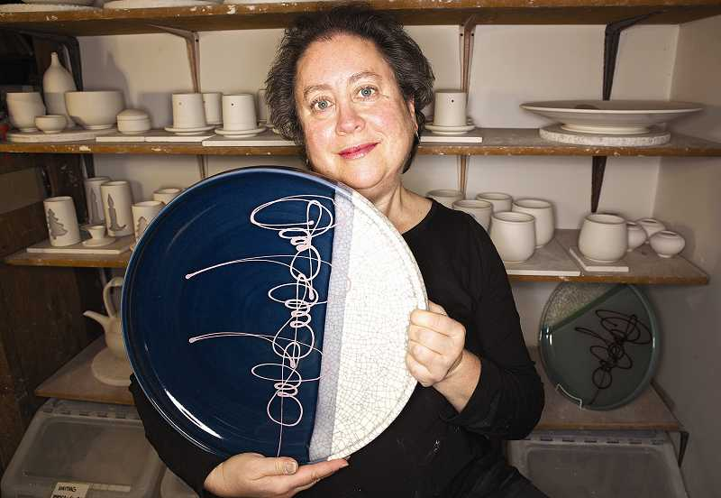 by: TIMES PHOTO: JAIME VALDEZ -  Deborah Shapiro holds a plate she made at her studio in Tigard. Her work is both beautiful and functional. Shapiro is participating in the annual Portland Open Studios and in the Washington County Open Studios.  TIMES PHOTO:  JAIME VALDEZ