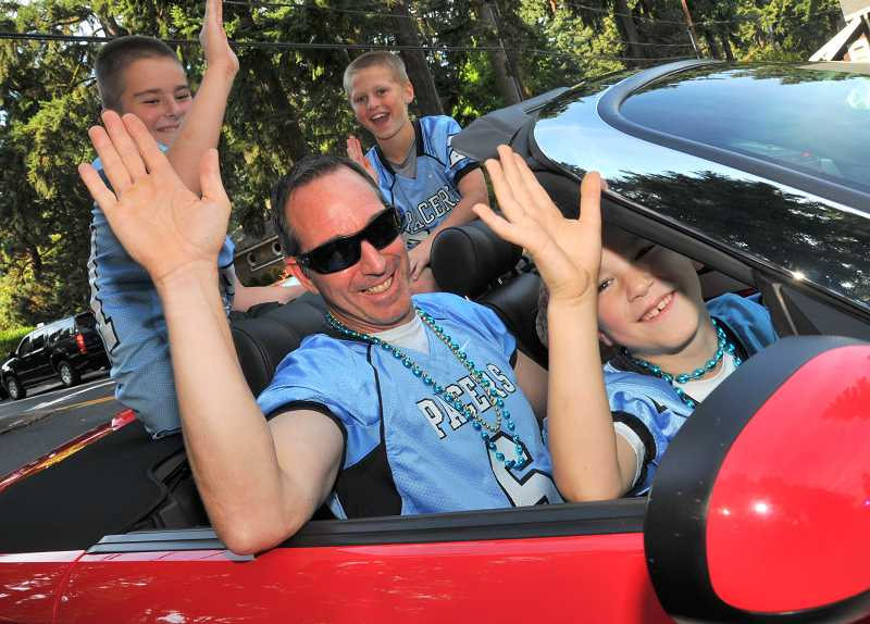 by: REVIEW PHOTO: VERN UYETAKE - Lakeridge Athletic Director Ian Lamont served as grand marshal of the parade. Riding with him are his sons, Owen, seated on his lap, and Luke, behind, and Thomas Dukart on the right.