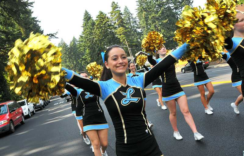 by: REVIEW PHOTO: VERN UYETAKE - Cheerleader Keana Pigg pumps up the crowd while walking in the parade.