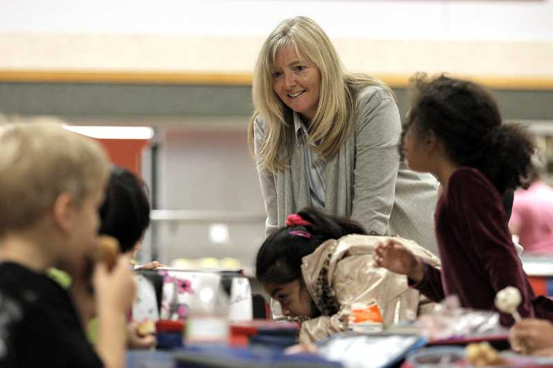 by: THE TIMES - JAIME VALDEZ - Bridgeport Elementary School principal Debbie Ebert checks in with students in the school cafeteria during lunch. Ebert is the former principal of Russell Academy in the Parkrose School District.