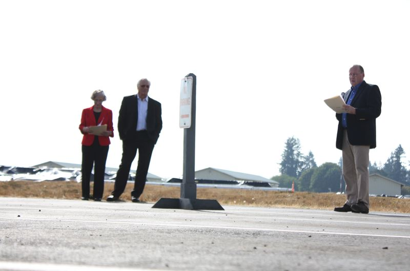 by: STOVER E. HARGER III - Standing in front of the Scappoose airport land that will soon house Oregon Aero's new hangar, Chief Operating Officer Tony Erickson speaks about his company's recent growth. Watching are company founders Jude and Mike Dennis.