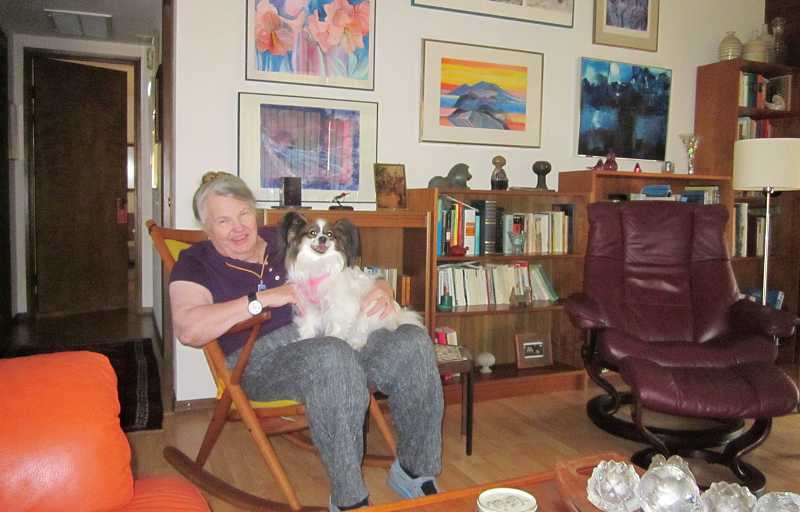by: BARBARA SHERMAN - BIG ON COLOR - Ann Stuller sits with one of her two Papillions, Desirée, in front of a wall in her living room filled mostly with her artwork.