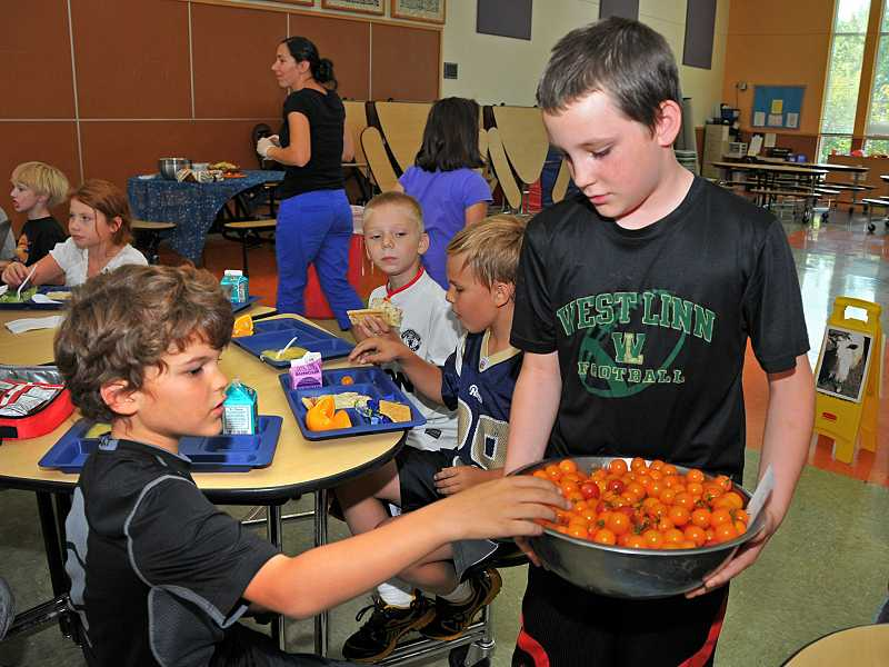 by: TIDINGS PHOTO: VERN UYETAKE - Fourth- grader Maximus Doman offers a tomato to third-grader Dale Herman.