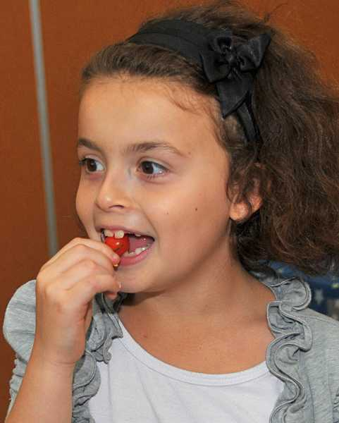 by: TIDINGS PHOTO: VERN UYETAKE  - Third-grader Napa Ayach enjoys a fresh cherry tomato.