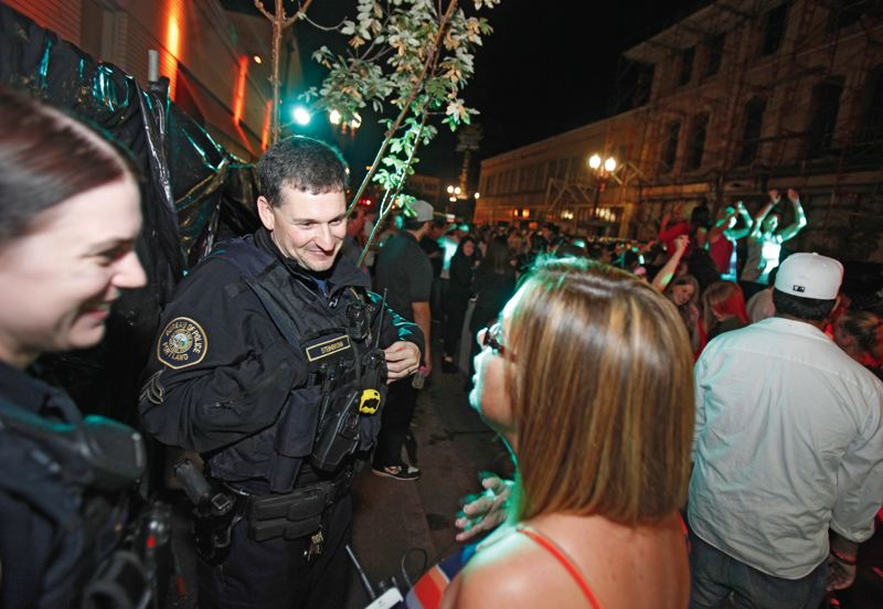 by: TRIBUNE PHOTO: JON HOUSE - Sgt. Rich Steinbronn and Officer Ariana Ridgley (left) chat with Splash Bar owner Jordan Ruemler, hosting a block party on Northwest Third and Couch on Friday night.