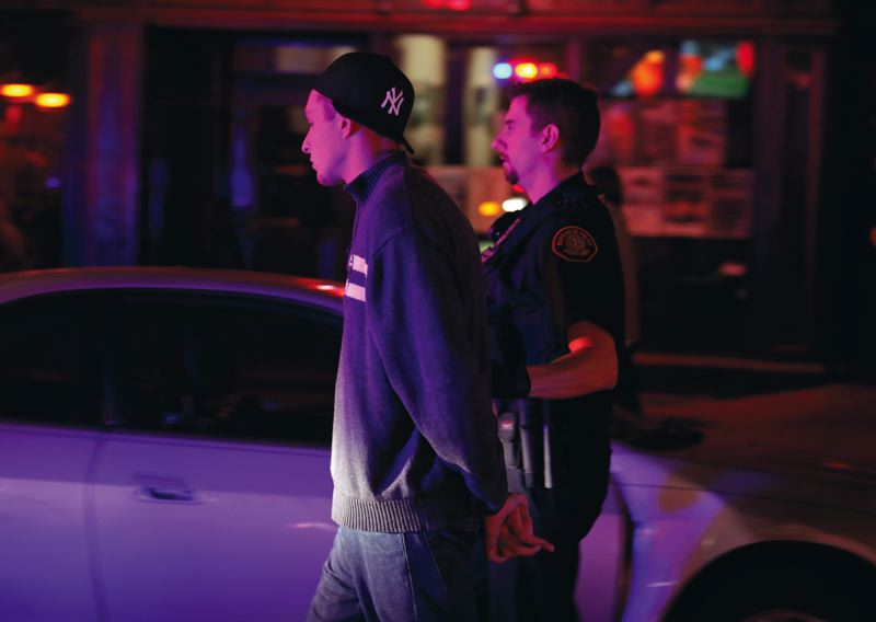by: TRIBUNE PHOTO: JON HOUSE - A man is arrested by officer Todd Harris after a bar fight outside Club XV ended with one combatant unconscious. Police are getting called four times a night - mostly about fights - to some Old Town clubs.