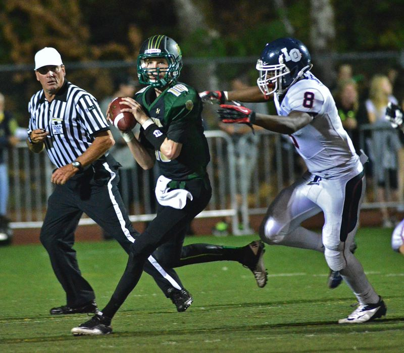 by: VERN UYETAKE - West Linn quarterback Hayden Coppedge runs away from a Lake Oswego defender while looking for an open receiver during last Friday's loss to the Lakers.