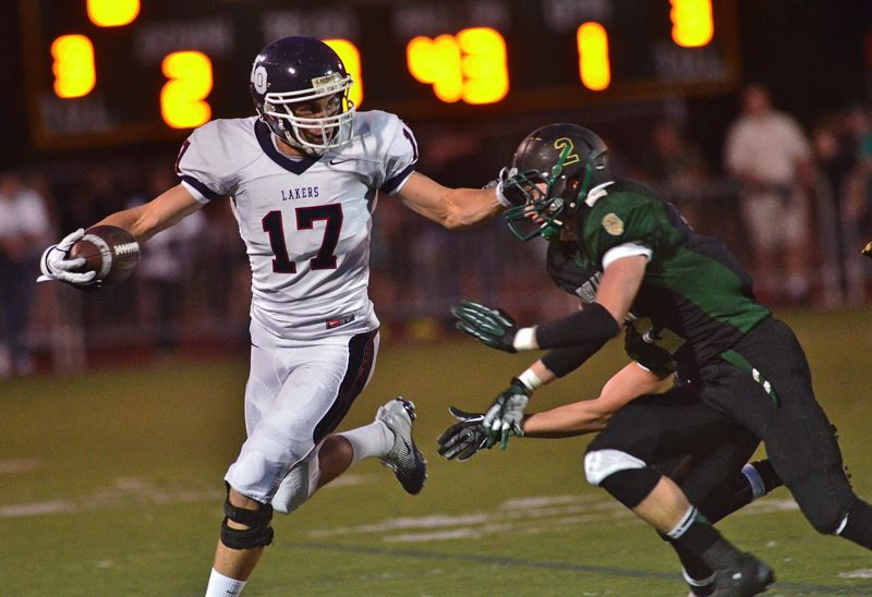 by: VERN UYETAKE - Lake Oswego receiver Connor Griffin fights off West Linn's Jarrod Howard after making a reception in last week's 41-0 win over the Lions.