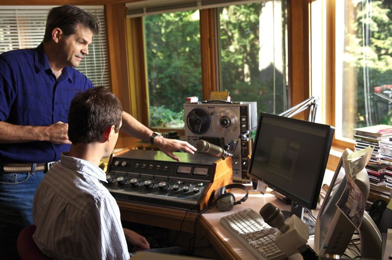by: JAIME VALDEZ - Ken Seymour and his son John, right, explain how to work the controls of the new KQRZ radio station in the basement of Ken's Cooper Mountain house.