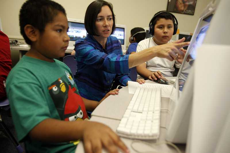 by: JONATHAN HOUSE - Jenny Takeda, a substitute teacher in the Beaverton School District, helps fourth-grader Alan Valdovinos Giron navigate a web page during a computer instruction session at William Walker Elementary School.