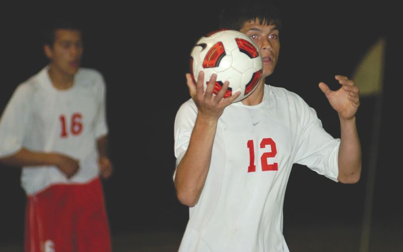 by: THE OUTLOOK: DAVID BALL - Centennials Adan Carrillo makes a throw-in during a 1-1 tie with Reynolds on Thursday night. Carrillo assisted on the Eagles' goal.