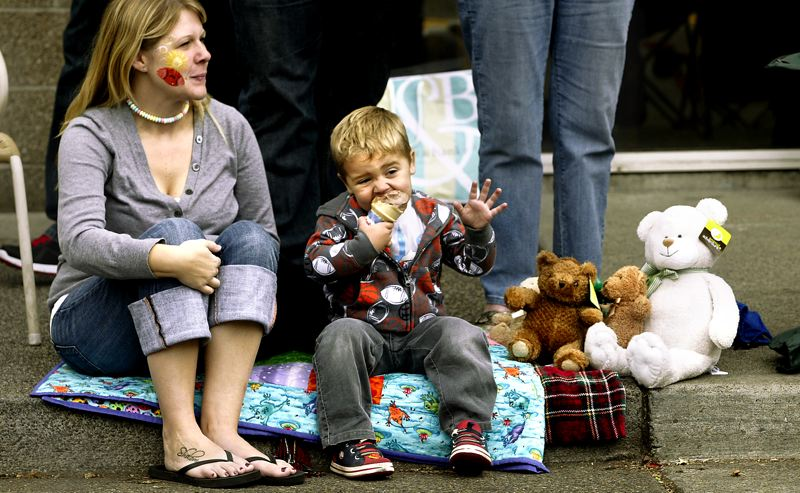 by: OUTLOOK PHOTO: JIM CLARK - Kalum Schenck doesn't let the Teddy Bear Parade slow down his enjoyment of a chocolate ice cream cone during the Teddy Bear Parade in downtown Gresham. Kalum attended the event with his mother Tiffany, left, and several stuffed friends.