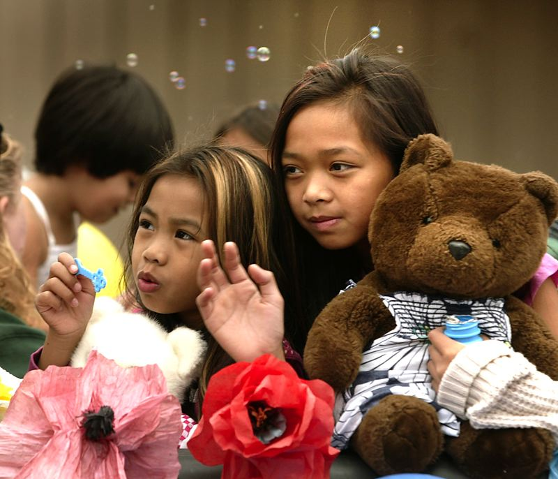 by: OUTLOOK PHOTO: JIM CLARK - Malani Boun, left, and her sister Sariah take part in the Teddy Bear Parade. They rode on the float representing Rockwood Center for Family Success.