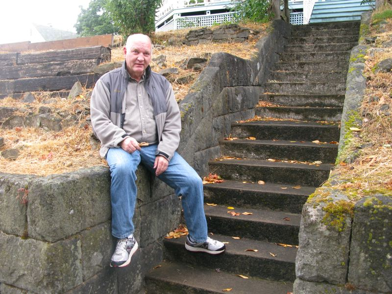 by: PHOTO BY RAYMOND RENDLEMAN - Oregon City native Paul Johnston sits on the spot on Washington Street where star actor George Maharis sat 50 years previously in filming Route 66.