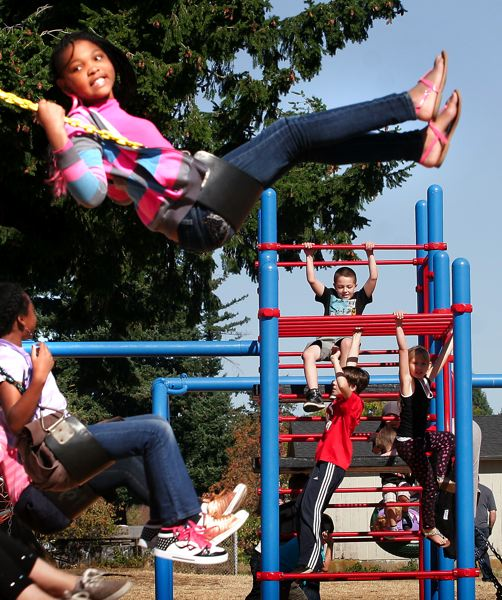 by: OUTLOOK PHOTO: JIM CLARK - Students at Oliver Elementary School enjoy the new playground. Old playground equipment was repainted, and new equipment was added.