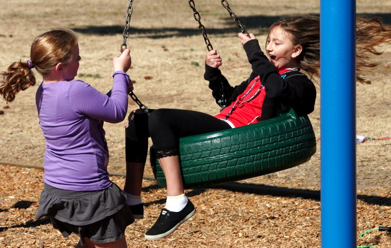 by: OUTLOOK PHOTO: JIM CLARK - Montana Fewell, left, and Morgan Flemming play in the new tire swing at Oliver Elementary School.
