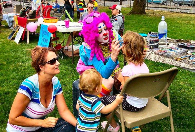 by: RITA A. LEONARD - Face painter Lee Loona works on Addison, age 4 - watched by mom Kirsten, and 11-month-old Knox.