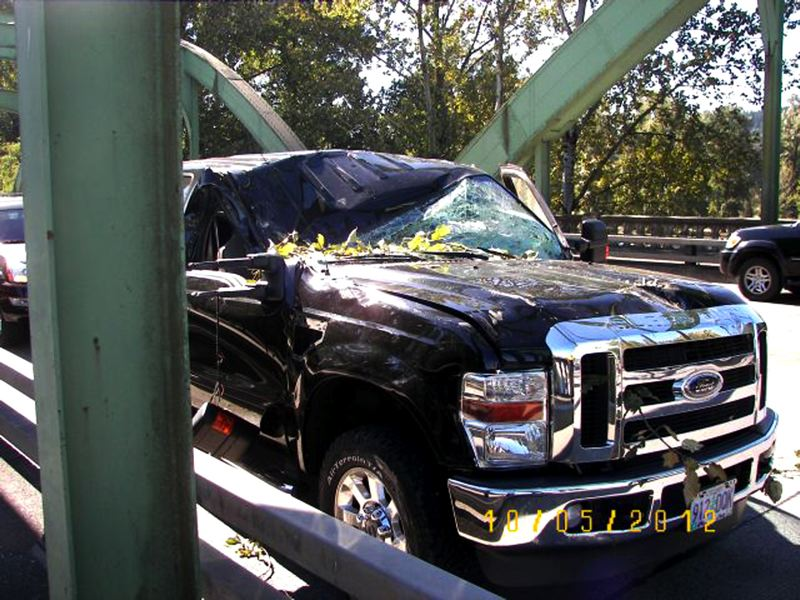 by: CONTRIBUTED PHOTO: OREGON STATE POLICE - Wind snapped a tree, which fell onto two vehicles, including this pickup. The driver, a Damascus man, was not seriously injured.