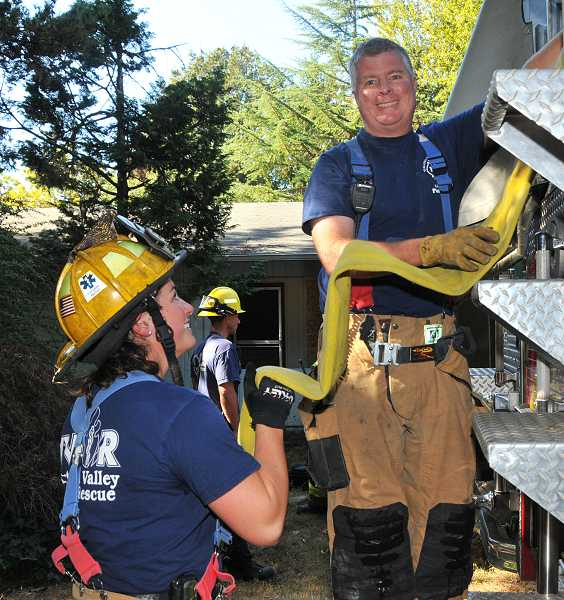 by: VERN UYETAKE - Tarah Roberts, left, and Dale Johnson load a water hose on a fire truck during a drill Oct. 8.