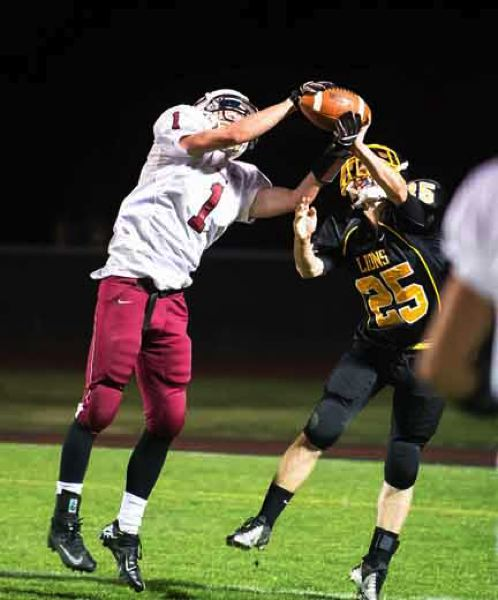 by: JEREMY DUECK - Sandy's Blake Robison hauls in a pass as St. Helens Ryan Jensen tries to break it up during Friday's game.