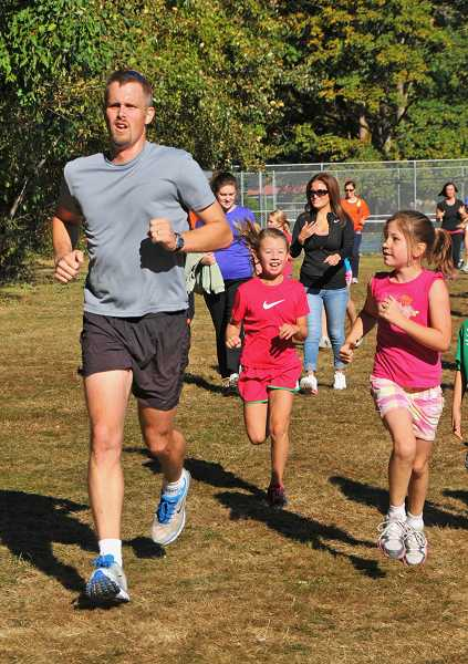 Principal Peter McDougal runs along with third-graders Anna Boyer, center, and Carley Moos.