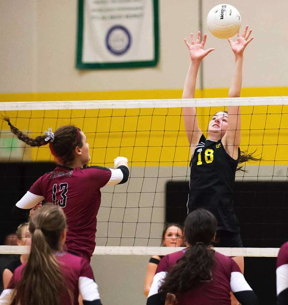 by: JEREMY DUECK - St. Helens' Taylor Albertson goes high to block during last week's NWOC match with Sherwood. The Lady Lions lost in five games.