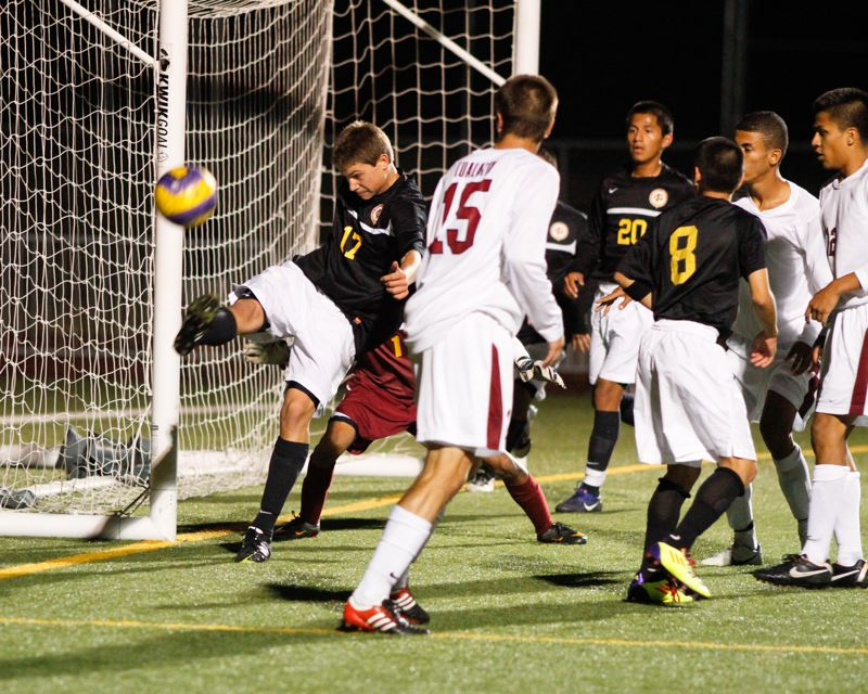 by: CHASE ALLGOOD - Forest Grove defender Ben Acord clears the ball away from the Viking's goal in Forest Grove's first loss of the season.