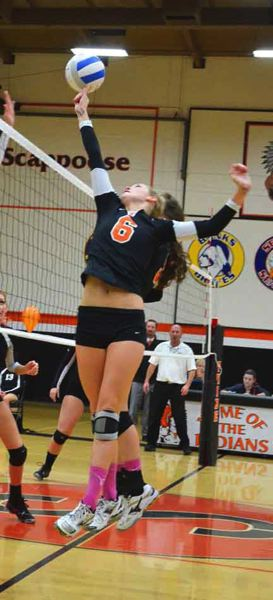 by: JOHN BREWINGTON - Scappoose's Phlycia Haigh tips the ball over the net during Monday's volleyball match with Tillamook.