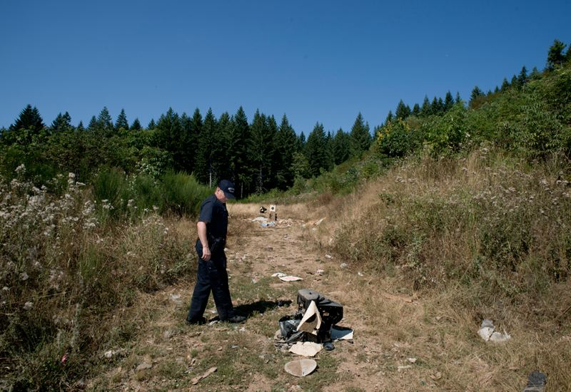 by: NEWS-TIMES PHOTO: CHASE ALLGOOD - Oregon State Trooper Roger Reid investigates a site west of Forest Grove that is used for shooting and target practice.