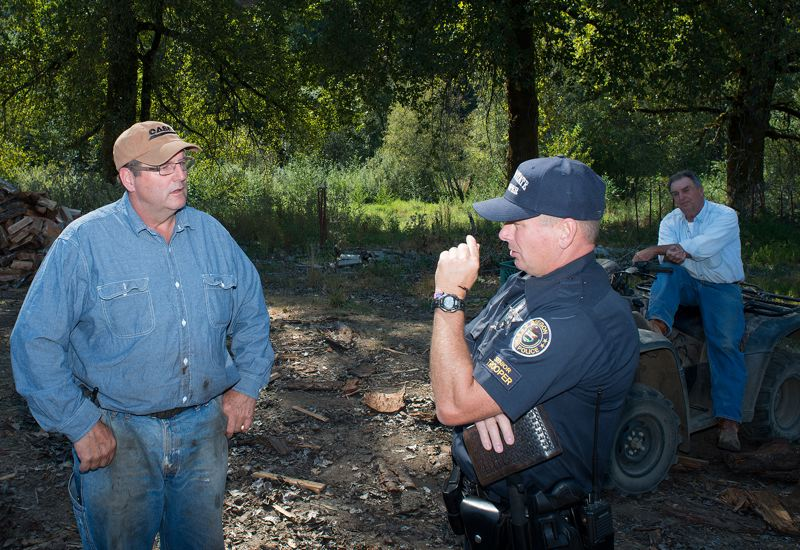 by: NEWS-TIMES PHOTO: CHASE ALLGOOD - Property owner Terry Howell discusses the threat of poachers on his land with Trooper Roger Reid.