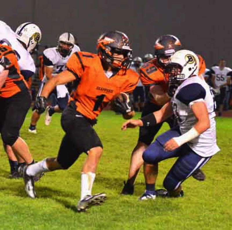 by: JOHN BREWINGTON - Scappoose's Carson Davison blows through a big hole in the line during Friday's game with Banks. Davison scored three times in the 54-29 win.