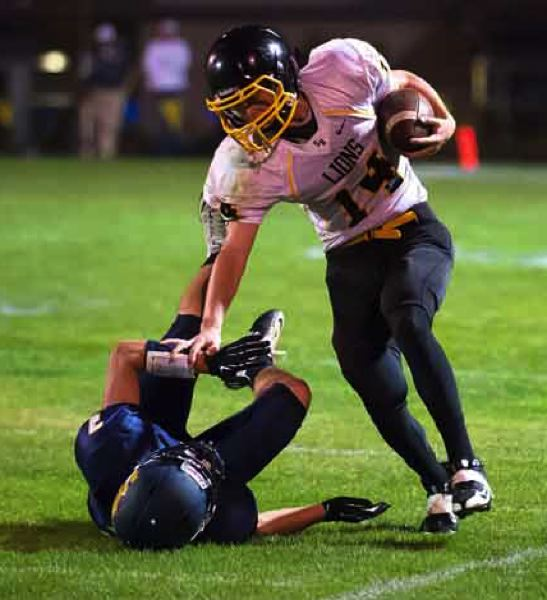 by: JEREMY DUECK - St. Helens' quarterback Gage Bumgardner stiff arms a Hood River Defender and picks up a first down during Friday's game. The Lions made it close for awhile in the first half, but eventually fell behind.