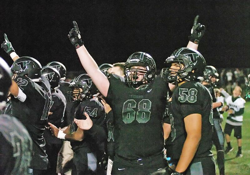 WE WIN -- Tigard senior Blake Chamberlain (68) celebrates with his teammates near the end of Friday's game.