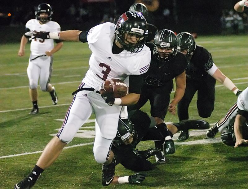 RUNNING STRONG -- Tualatin High School senior Andrew Schlottmann looks for running room in the first quarter of Friday's game at Tigard. Schlottmann rushed for 109 yards on 21 carries in the contest.
