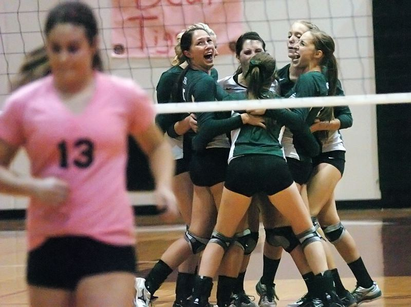 by: DAN BROOD - THAT'S ONE -- The Tigard High School volleyball team celebrates after rallying for a game one victory in Tuesday's match.