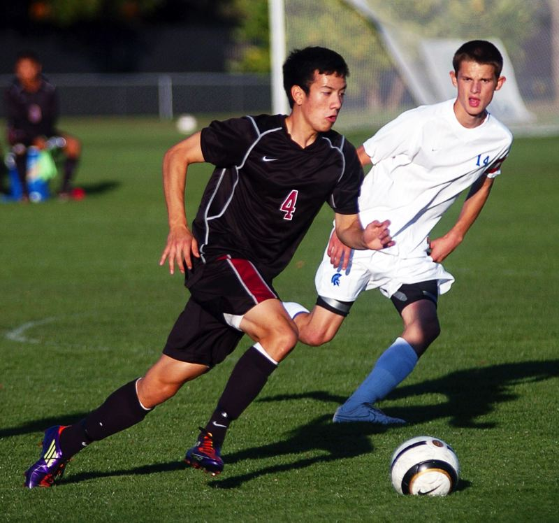 by: DAN BROOD - TURNING IT ON -- Tualatin senior Jonathan Thayer (left) looks to sprint past Hillsboro junior Aaron Barber-Axhelm in last week's match. The Wolves rallied from a 2-0 defecit to tie the match before falling 3-2.