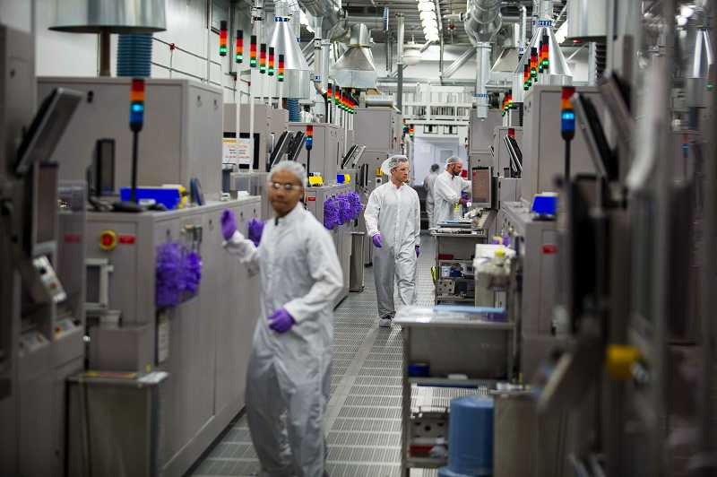 by: CHRISTOPHER ONSTOTT - SolarWorld employees manufacture high-performance solar cells at the company's Hillsboro plant.