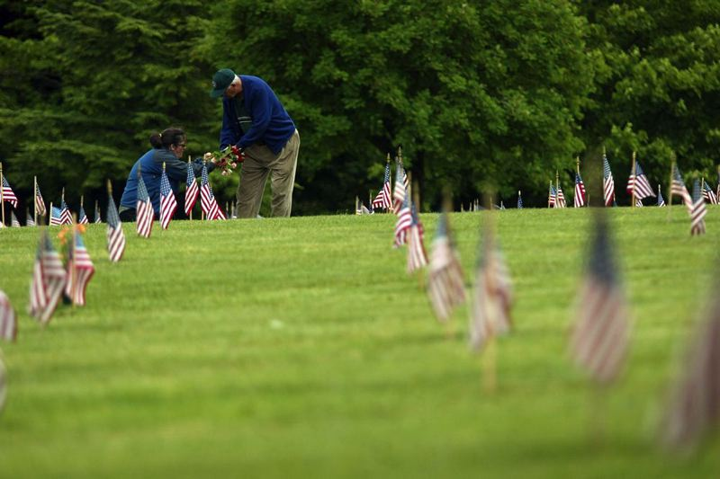 by: TRIBUNE FILE PHOTO: CHRISTOPHER ONSTOTT - Mary Beth Pinder and retired U.S. Air Force veteran Bob Pinder lay flowers on the grave of his Bob's uncle Lawrence Pinder, an army veteran of World War II in Willamette National Cemetery during the 2006 Memorial Day weekend.