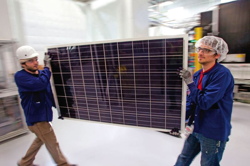 by: TRIBUNE PHOTO: CHRISTOPHER ONSTOTT - Solar World workers transfer a solar panel to the next step in the production process at the German company's Hillsboro plant. Some critics say their products are too expensive, a charge the company denies.