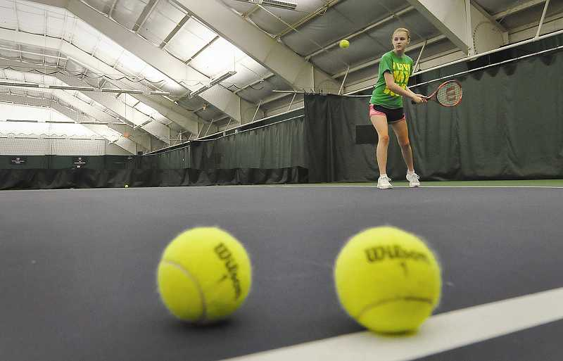 by: VERN UYETAKE - Anna Lesa Fisher plays tennis during a lesson at the Lake Oswego Indoor Tennis Center on Diane Drive. The four-court building is often in high demand, officials say, leading the city to seek a larger, replacement facility in the Stafford area.